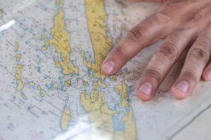 Segler prüft Kurs auf Seekarte